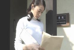 玄関先に置いてある封筒を手に取る真知子