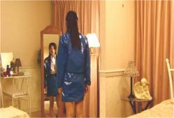 鏡に映った星川先生の姿を見ている青井マキノ