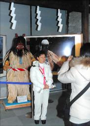 イ・ビョンホンさんが着たなまはげの衣装の前で記念撮影をする韓国人観光客