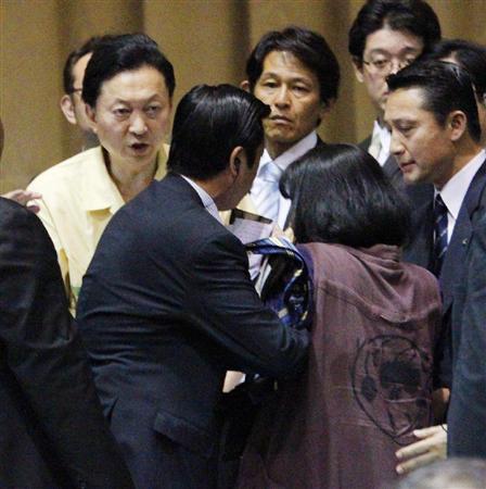 市民との「対話集会」終了後、鳩山首相に駆け寄り制止される女性(右から2人目)=4日午後、沖縄県宜野湾市の市立普天間第二小学校