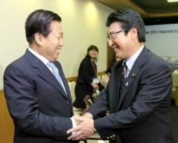 支那の周生賢環境保護相(左)を握手で迎える小沢環境相=22日午後、千歳市