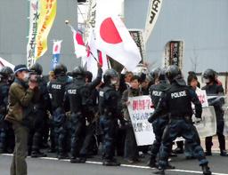 警察官に囲まれながら京都朝鮮第一初級学校までデモ行進する在特会のメンバーら=3月28日午後、京都市南区