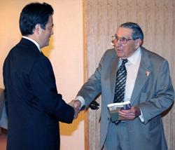 来日し岡田克也外相と握手する元米兵捕虜のレスター・テニーさん(右)=外務省で2010年9月13日午前