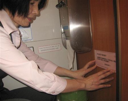 浅草寺の個室トイレで新しい中国語の張り紙を張る女性職員=18日午前、東京都台東区