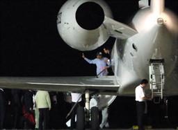 中国政府のチャーター機にVサインを掲げながら乗り込む船長と見られる男性=25日午前1時56分、沖縄県石垣市の石垣空港