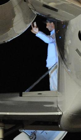 尖閣諸島沖で衝突事故を起こした中国人船長が、処分保留で釈放。チャーター機搭乗前に両手でピースサインをする=25日午前1時56分、沖縄県石垣市
