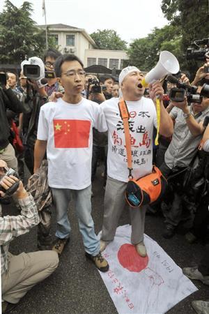 北京の日本大使館前で日の丸を踏みつけ、抗議する男性=18日午前、北京や上海で反日デモ