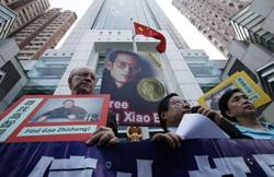 香港の中国政府の出先機関前で、劉暁波氏の釈放を求め同氏の写真を掲げる民主活動家ら=2010年10月11日