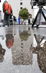 雨の降る中、第5管区海上保安本部が入る合同庁舎前に集まる報道陣ら=2010年11月12日