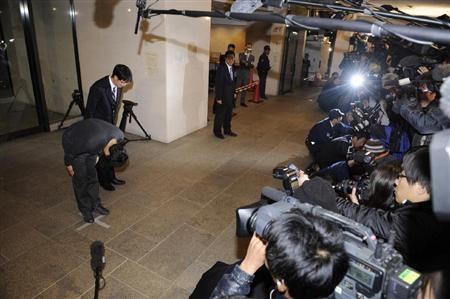 支那漁船体当たり映像公開問題で、神戸海上保安部が入った合同庁舎前で頭を下げる海上保安官=16日午前1時26分、神戸市中央区