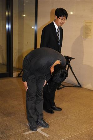 弁護士(右)とともに報道陣の前に姿を見せ、頭を下げる海上保安官=16日未明、神戸市中央区
