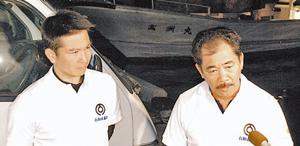 尖閣諸島から帰港後、記者団の質問に答える仲間(右)、箕底両市議=10日、石垣市・登野城漁港