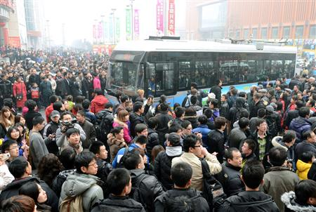 北京市の目抜き通り、王府井に集まった人々と、警察の誘導で通過する公共バス=20日