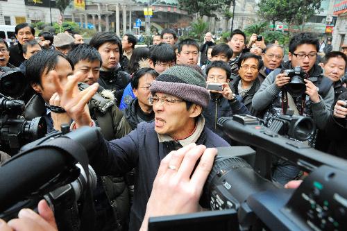 民主化を求めるデモの呼びかけに応じて集まり、警察署前で法治の不備などを訴える男性。この直前に大学生ら少なくとも3人が連行された=20日午後2時16分、上海市中心部の人民広場周辺