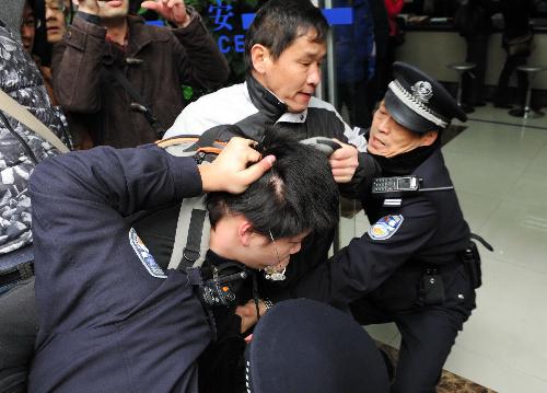 民主化を求めるデモの呼びかけに応じて集まり、警察官に連行される若者(中央)。直後に警察署前で法治の不備を訴える抗議活動が始まり、さらに男性が連行された=20日午後2時11分、上海市中心部の人民広場周辺