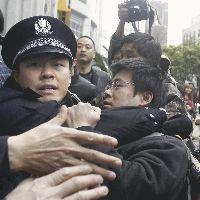 上海で、集会が予定された現場から警官に連行される男性(右