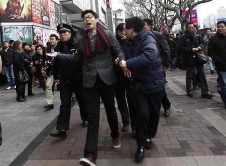 中国でNHKニュース中断 「中国ジャスミン革命」呼び掛けで 20日、上海市の路上で警察に連行される男性