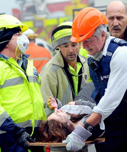 クライストチャーチで22日、救助隊員に運ばれる負傷者=AP