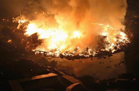 夜になっても燃え続ける家屋など=11日午後9時15分、宮城県名取市で共同通信社ヘリから