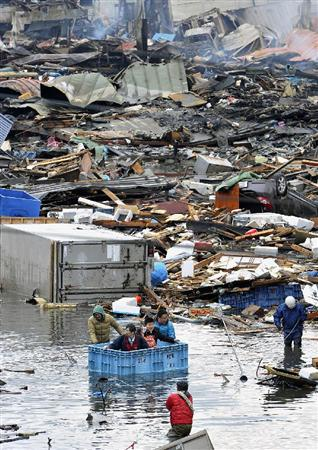 魚を入れるコンテナを使って救助される、建物に取り残されていた人たち=12日午前、宮城県気仙沼市