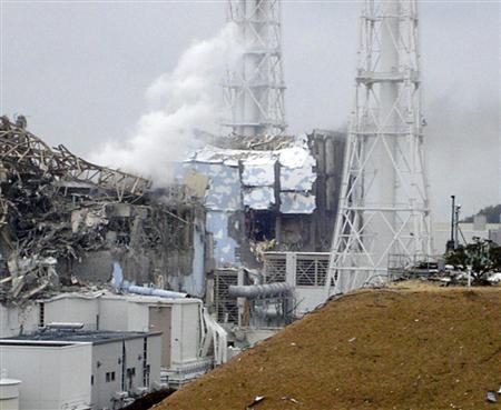 15日に撮影された白煙を上げる東京電力福島第1原発3号機(左)。中央奥は4号機(東京電力提供)