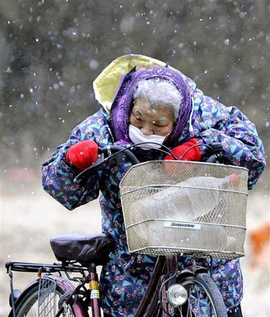 雪が舞う中、自転車で水を運ぶお年寄り=16日午後、岩手県陸前高田市
