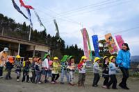 鯉のぼりが泳ぐ陸前高田市の下矢作保育園で子どもたちと遊ぶアグネス大使