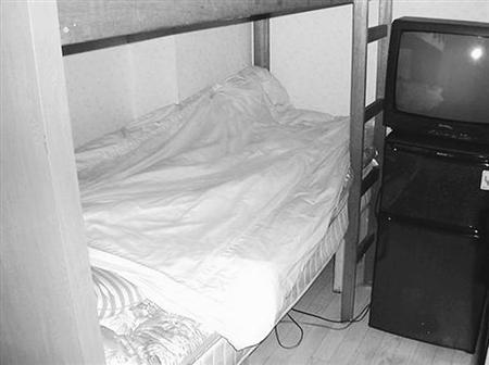 山中さんの住む繁華街のゲストルーム。ベッドとテレビのほかはなく、殺風景。絶えず喧噪が聞こえてくる