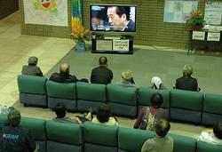 内閣不信任決議案の提出について報じるニュース番組を食い入るように見つめる避難住民ら=福島市のあづま総合体育館で2011年6月1日、伊澤拓也撮影