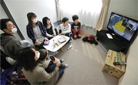 仮設住宅に入居し、部屋でテレビを見る家族。一刻も早い住宅建設が望まれる=4月11日、岩手県陸前高田市