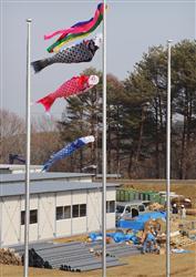 岩手県宮古市の避難所近くにあるグランドでは、急ピッチで仮設住宅が建設され、敷地内ではこいのぼりが風に舞っていた=4月14日