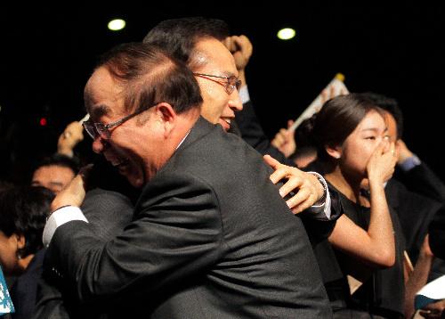 2018年冬季五輪の開催地に韓国・平昌が選ばれ、招致関係者と抱き合う李明博大統領(左)。右奥はフィギュアスケートのキムヨナ金妍児選手