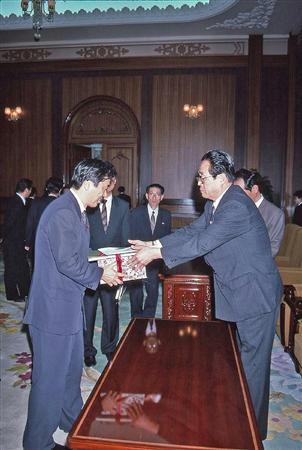 菅首相(左)は1995年3月に訪朝し、北朝鮮の金容淳党国際部長からプレゼントを受け取った(山本皓一氏撮影)