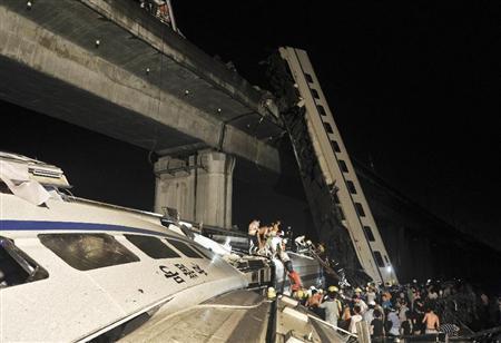 中国浙江省で高速鉄道の車両が橋から転落し、乗客の救助作業に当たる人たち=23日夜(AP)