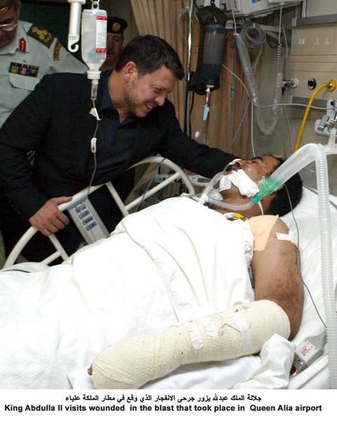 毎日新聞によるクラスター爆弾爆発事件で負傷した被害者を見舞うヨルダンのアブドラ国王