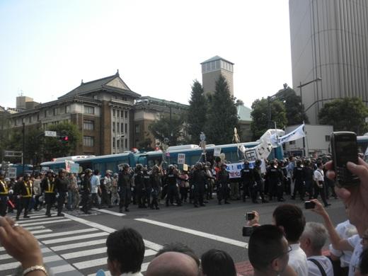 靖国通りから九段下交差点を右折して目白通りに入るマジキチ「反天連デモ」後ろに見える昭和館(右)と九段会館(左)の向こうには皇居がある。