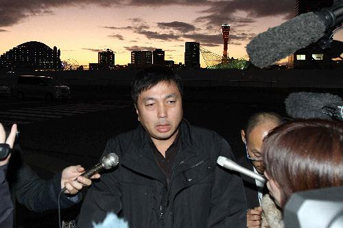 第五管区海上保安本部から出て記者に囲まれる一色正春・海上保安官=22日午後、神戸市中央区
