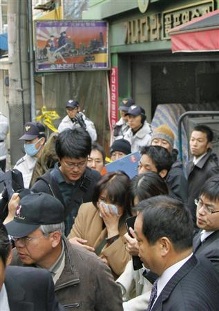 火災があった室内射撃場の入るビルを訪れた被害者の家族ら
