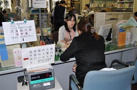 子ども手当の申請方法を問い合わせる外国人=東京都豊島区東池袋の豊島区役所