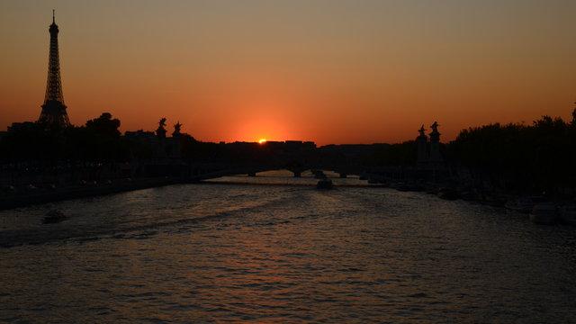 セーヌ川やアレクサンドル3世橋やエッフェル塔の日暮れ