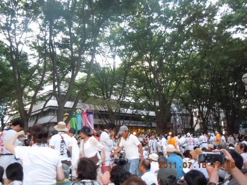 パレードを続けるか協議中の出場者など目に入らないかのように、座って並ぶ客の前をさえぎって歩行を続ける人たち