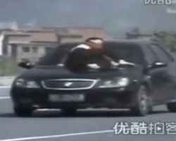 Crazy Chinese woman jumps on hood of fleeing car