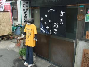 かきおこ「安良田」 お店の前にはかかし?