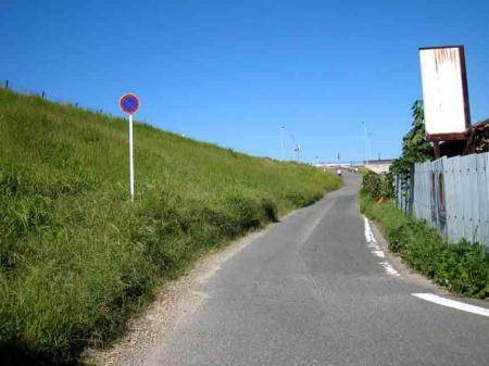 堤防道路脇のカーブする坂道