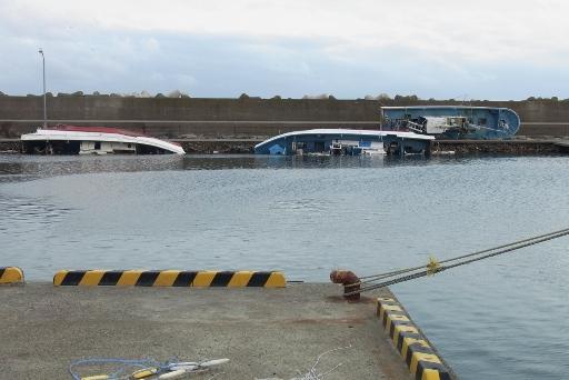 堤防に横たわる漁船が